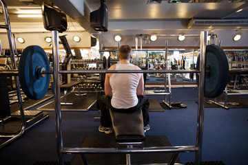 Homme assis de dos sur un banc de musculation