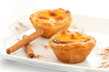 Custard Pies over a white plate with cinnamon sticks