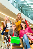 Four female friends shopping in a mall with wheelchair