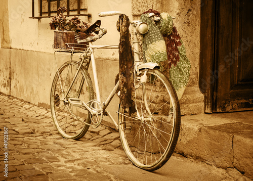 Deurstickers Fiets Vintage bicycle leaning against an old door in a medieval street