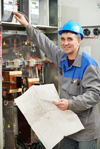 Happy electrician working at power line box