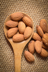 Almonds in a Wodden Spoon on a Burlap Background