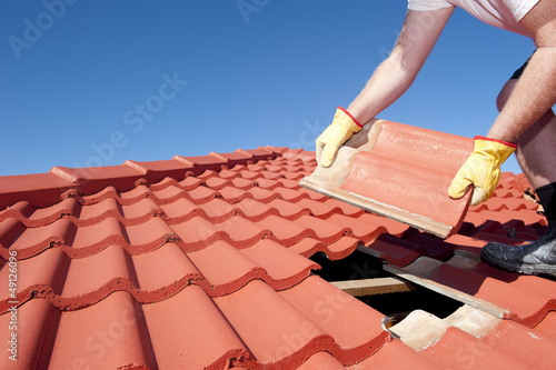 Leinwanddruck Bild Construction worker tile roofing repair