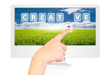 Hand pushing Creative word on monitor screen.