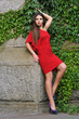 Fashion model posing in short red dress in the park