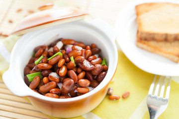 brown beans with onion in a ceramic pot