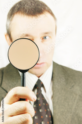 Man looks through a magnifying glass