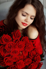Portrait of attractive Caucasian smiling woman with red roses bo