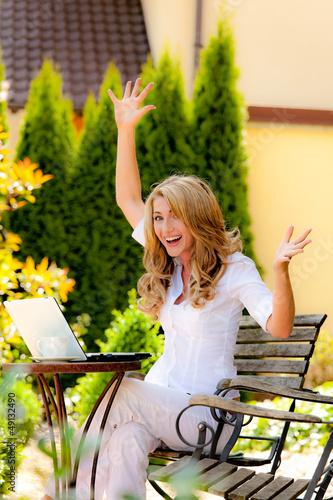 Erfolgreiche, lachende Frau mit Laptop im Garten