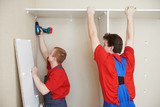 Wardrobe joiners at installation work poster