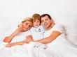 Familie liegt am Morgen im Bett