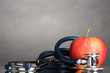 Medical stethoscope and red apple on grey