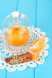 Tangerine on saucer under glass cover on blue background