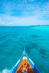 Maldivian wooden dhoni and clean ocean water and tropical island