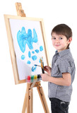 Little boy painting paints picture on easel isolated on white