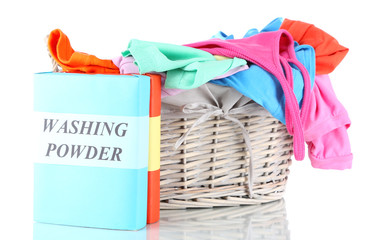 Clothes with washing powder in wooden basket isolated on white