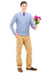 Full length portrait of a young romantic man holding a bouquet o