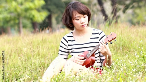 Thai woman with Ukulele in meadow