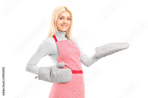 Young houswife wearing cooking mittens and apron