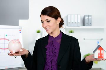geschäftsfrau hält haus und sparschwein in den händen