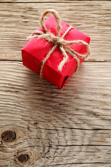 Gift box wrapped in red paper on wooden background