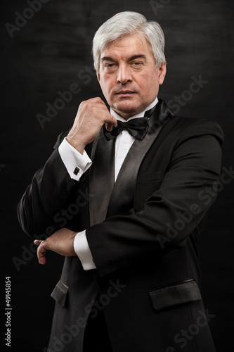 Portrait of handsome mature business leader over black backgroun