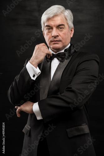 Portrait of handsome mature business leader over black backgroun