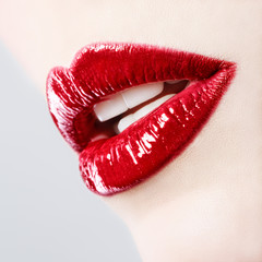 Beautiful female with red shiny lips close up