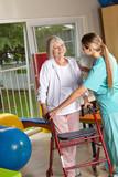 Physiotherapeutin erklärt Seniorin einen Rollator