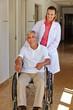 Altenpflegerin mit Senior im Rollstuhl