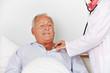 Senior wird mit Stethoskop abgehört