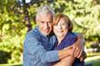 Altes Ehepaar umarmt sich im Park