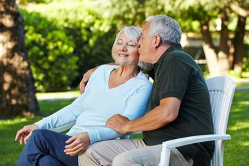 Senior küsst seine Frau im Garten