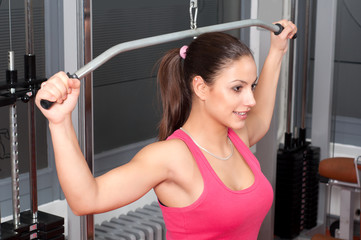 Beautiful young woman exercising with weights in the gym
