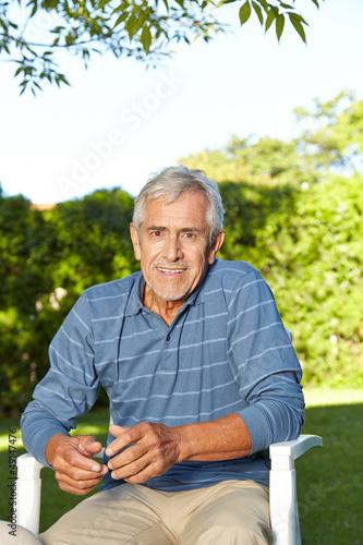 Senior sitzt im Sommer im Garten