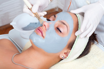 Beautiful young woman lying on massage table withfacial mask