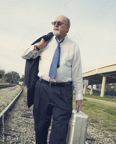 Angry, jobless senior businessman walking along railroad tracks