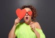 surprised curly woman cover eyes with two red hearts