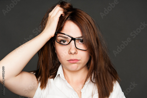 tired young woman in glasses