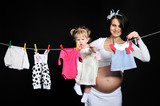 Pregnant young mother with her little baby girl hanging clothes