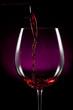 Llenando la copa de vino sobre fondo negro