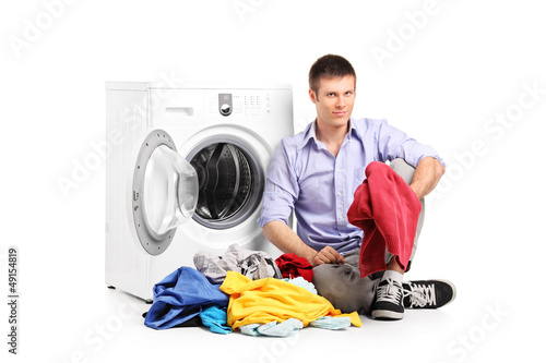 A young male sitting next to a washing machine
