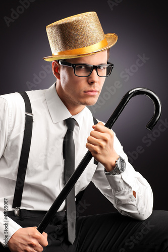 Portrait of a stylish man with hat holding a cane
