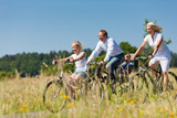 Fototapety Family cycling outdoors in summer