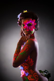 Pretty young woman in glowing flowers - uv light
