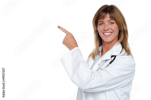 Cheerful female doctor pointing away
