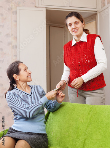 woman gives money to her mature mother