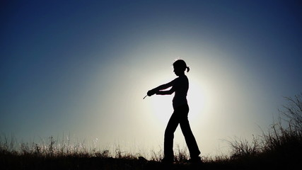 Silhouette of Girl Practicing With Sword