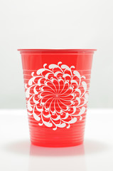 Red color plastic cup with geometric flower draw