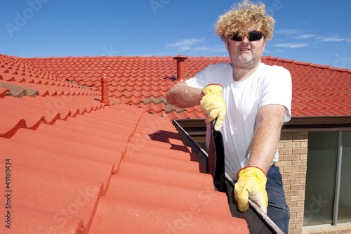 Man seasonal Gutter cleaning red roof